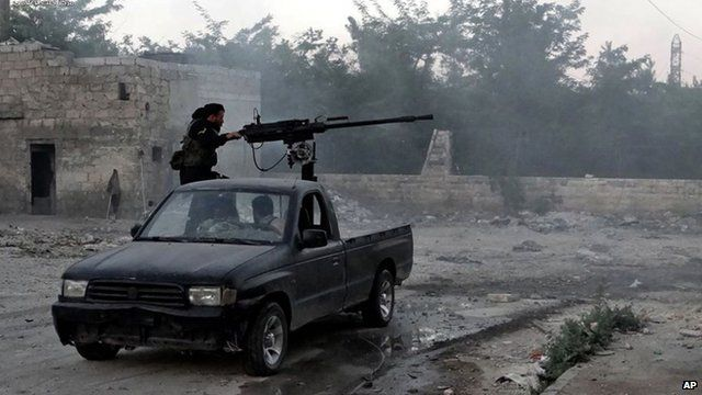 A Syrian rebel fires a heavy machine gun