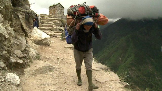 A porter going up a peak in Nepal