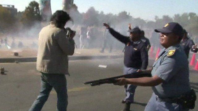 A police officer holding a gun at an anti-US demonstration in Soweto