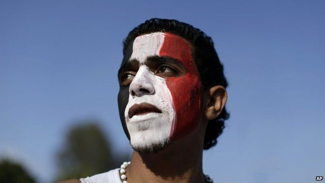 An opponent of Egypt's Islamist President Mohammed Morsi with his face painted with the colours of the Egyptian flag stands outside the presidential palace in Cairo.