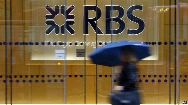 A woman walking past the headquarters of the Royal Bank of Scotland in the City of London