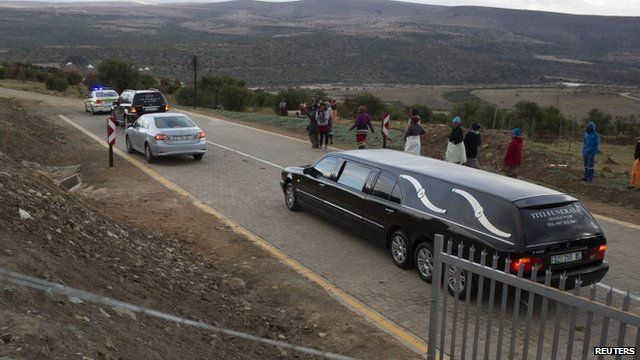 A convoy of police and funeral vehicles approaches the homestead of Mandla Mandela