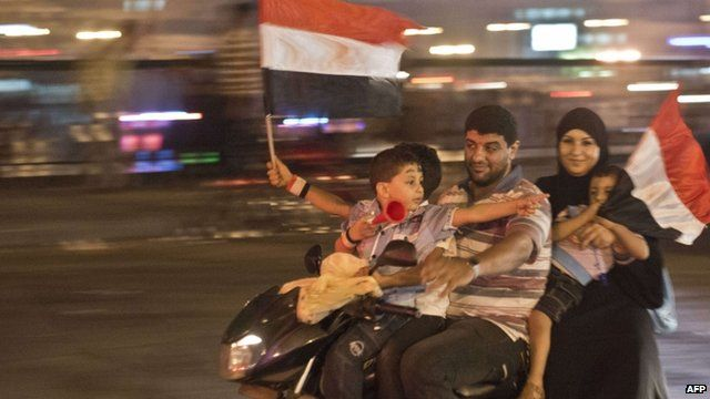 An Egyptian family on motorcycle celebrates in Cairo