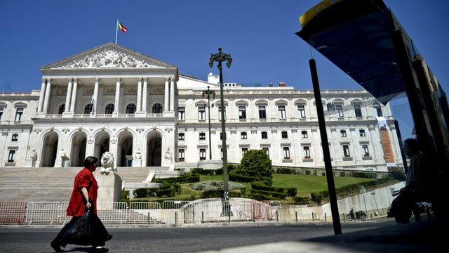 A woman walks by the Portuguese Parliament in Lisbon