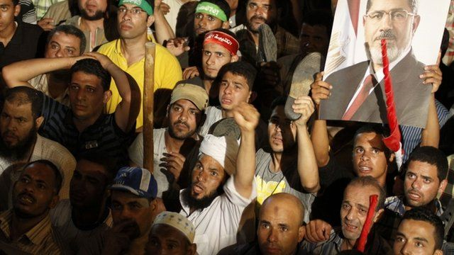 """Supporters of Egypt""""s ousted president Mohammed Morsi react after the Minister of Defence's announcement on state television Wednesday, July 3, 2013"""