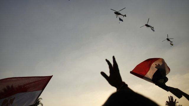 Egyptian military helicopters fly in formation over Tahrir Square in Cairo, Egypt