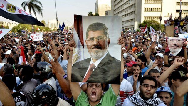 Egyptian supporters of the Muslim Brotherhood hold pictures of deposed president Mohamed Morsi