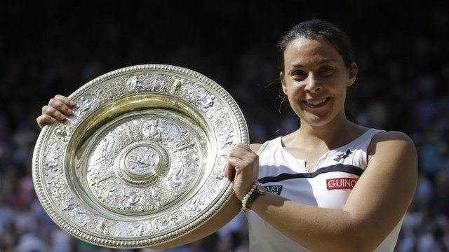 Marion Bartoli of France smiles as she holds the trophy after winning the Women's singles final match