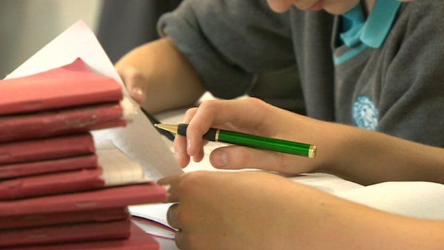 Pupil holds pen next to pile of school books