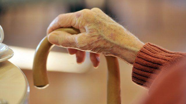 Elderly person holds walking stick