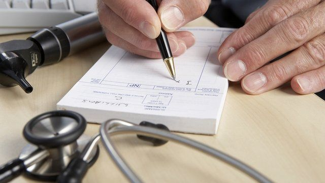 General practice doctor writing a prescription