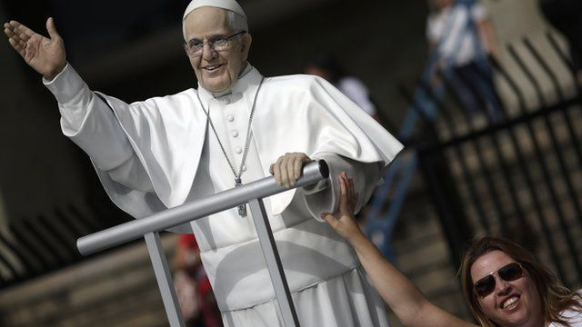 A woman poses with a statue of the Pope Francis in Rio de Janeiro
