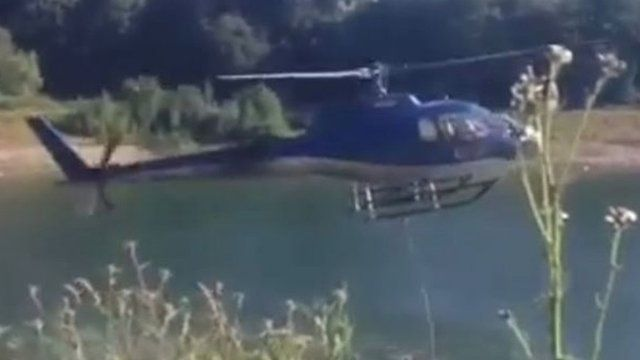 The helicopter picking up water