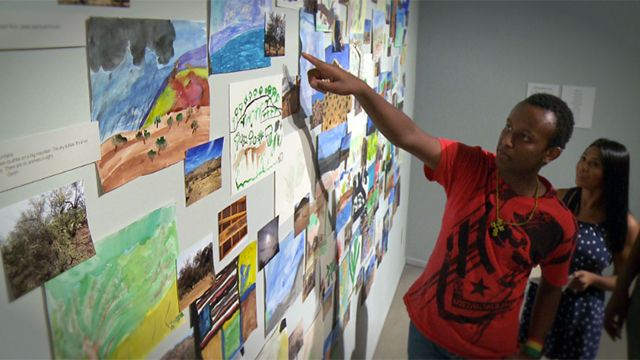 Ethiopian refugee points at artwork on the wall.
