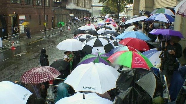 The world's media with umbrellas outside hospital