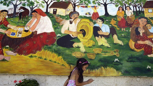 A girl walks by a Roma mural in Hungary