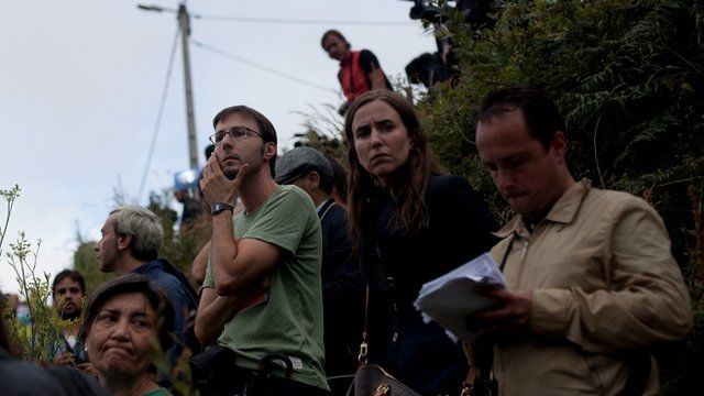 People watch at the scene of a train crash at Angrois near Santiago de Compostela, Spain