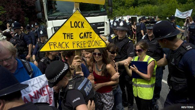 Demonstrators attempt to prevent police officers escorting a lorry to a drilling site