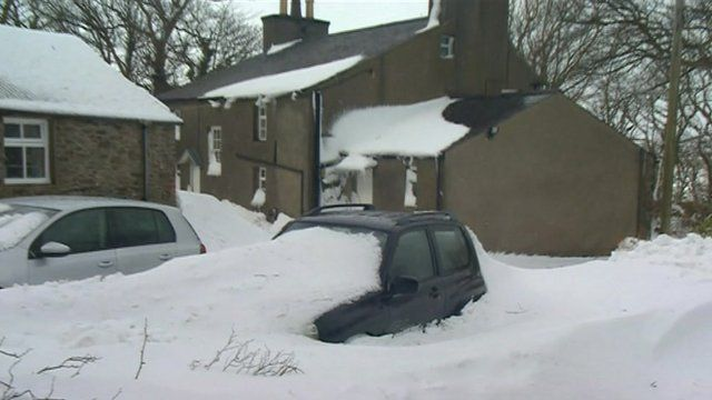 Car part-buried by snow drifts outside house
