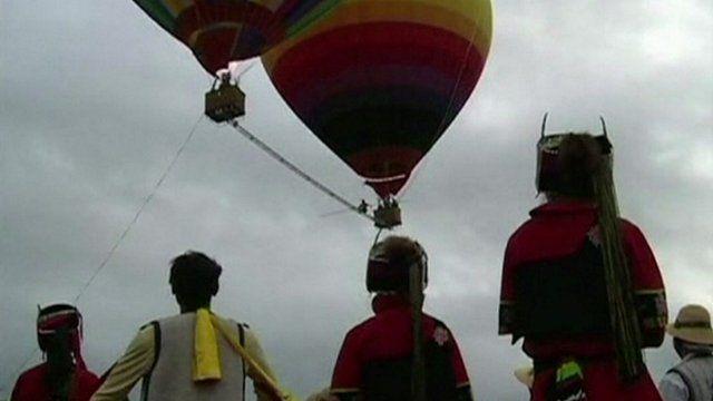Aisikaier Wubulikaisimu walking between two air balloons