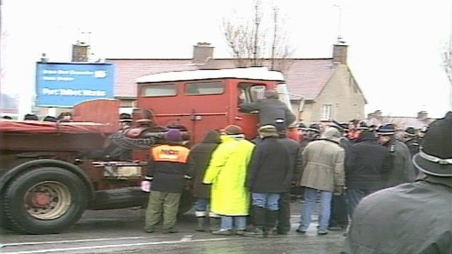 Police and striking miners surround a lorry