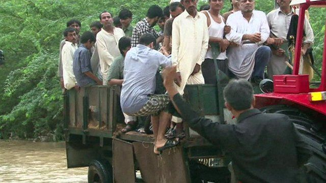 A man gets on a tractor which rescues flood victims in Karachi, Pakistan