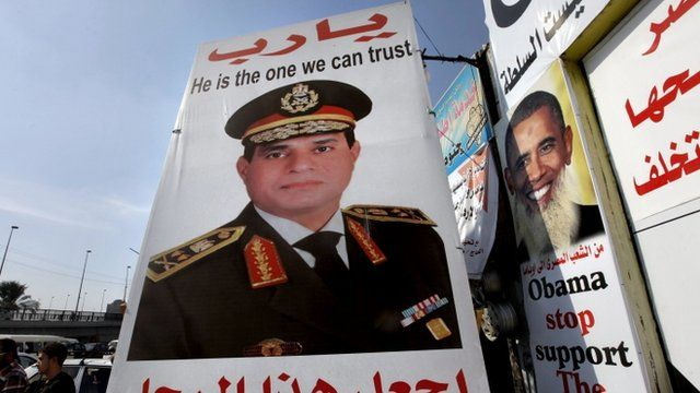"""Egyptians walk behind a banner depicting U.S President Barak Obama, right, and a banner supporting Egyptian Army Chief Lt. Gen. Abdel-Fattah el-Sissi, center, with Arabic that reads, """"God, keep this truthful honest man,"""" in Cairo, Egypt"""