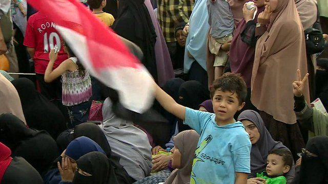 Boy waving Egyptian flag in crowd of mothers and children