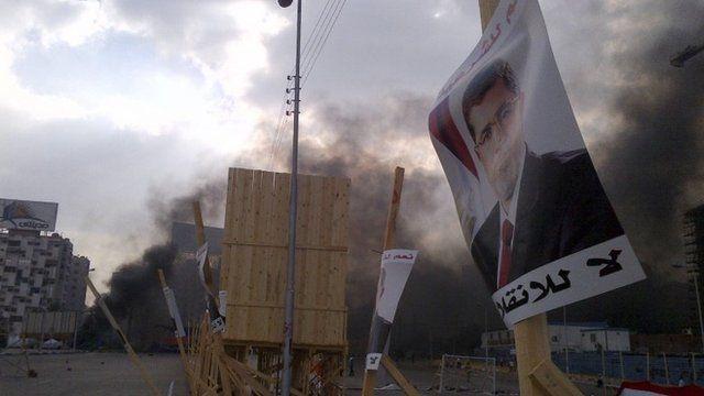 A poster of deposed Islamist President Mursi and rising smoke near the Rabba el Adwia Square