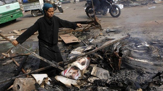 Woman standing by burned posters