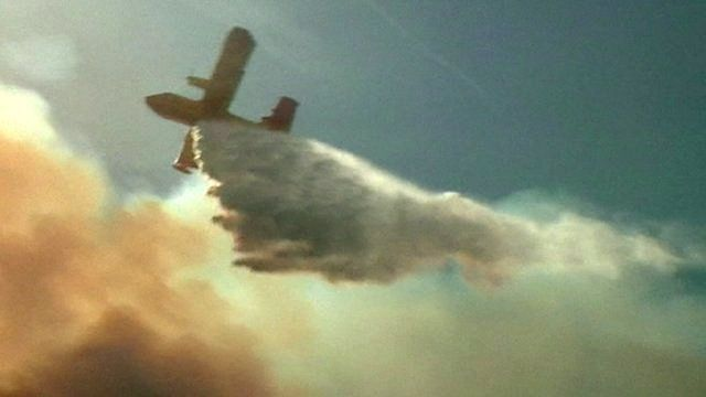 A water-bombing plane flying over a wildfire