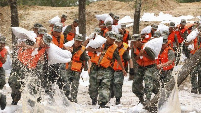 Soldiers rush to set up sand bags to prevent flood from an overflowing river in Heihe, Heilongjiang province, China