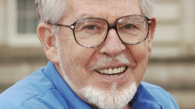 Rolf Harris wearing glasses and a blue shirt