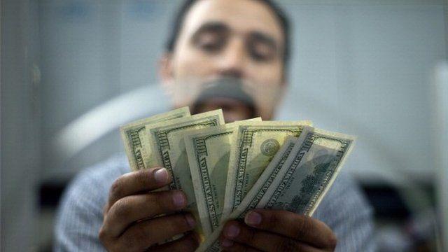 Indian moneychanger handling dollar bills