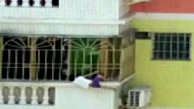 Child clings to balcony edge