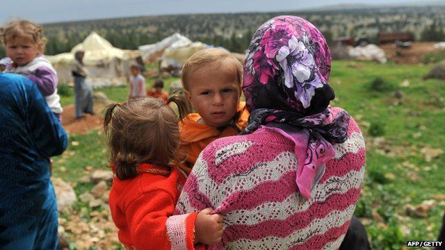 A Syrian woman carries her children near their makeshift refugee camp at the mountains of the city of Afrin, on the Syria-Turkey border, on March 28, 2013