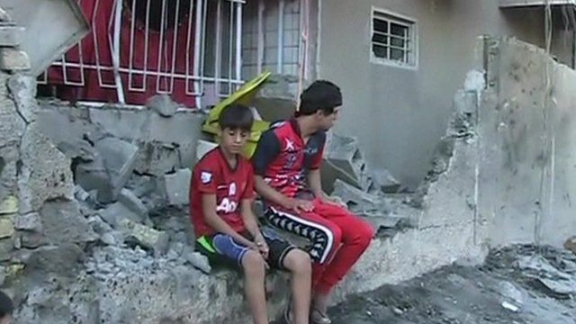 Boys sit in the rubble of a building in Baghdad