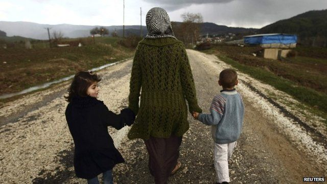 A Syrian woman walks with her children outside a refugee camp near the Turkish-Syrian border