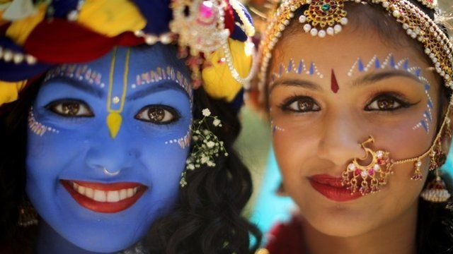 Laxmipriya Patel (L), aged 20, dressed as the Hindu god Lord Krishna, poses with her sister Mohini Pate