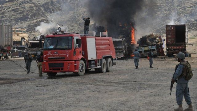 Afghan security personnel stand alert near burnt military vehicles after the clash