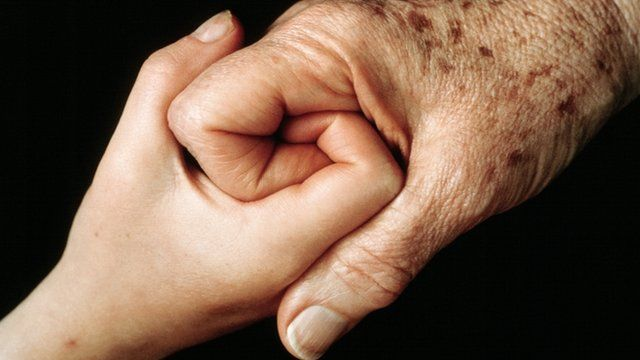 Older person holding hands with child