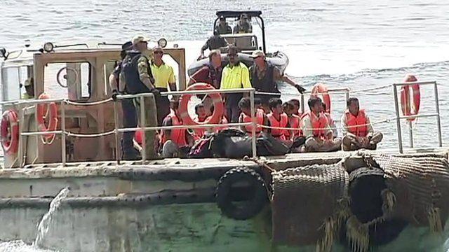 People wearing orange life jackets aboard a boat.