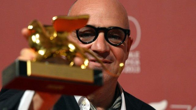 "Italian director Gianfranco Rosi poses with the Golden Lion for Best Film for his movie ""Sacro Gra"" during the award ceremony of the 70th Venice Film Festival on September 7"