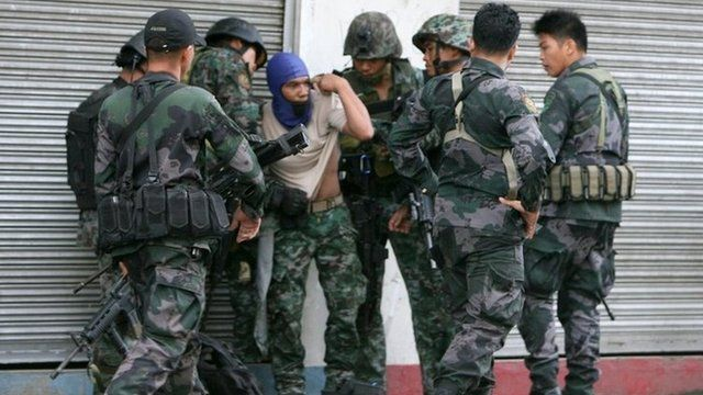Combat police forces check on their comrade (centre) who was hit by sniper fire in downtown Zamboanga in the Philippines on 9 September 2013