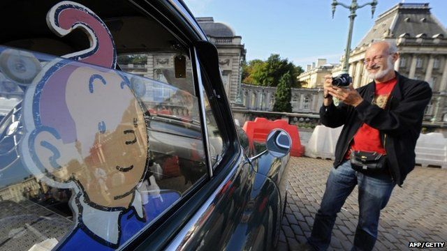 """A man takes a picture of a vehicle of """"Tintin magazine"""" car rally on September 8, 2013 in Brussels."""
