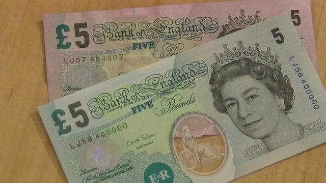 A plastic five pound note on top of a paper note.