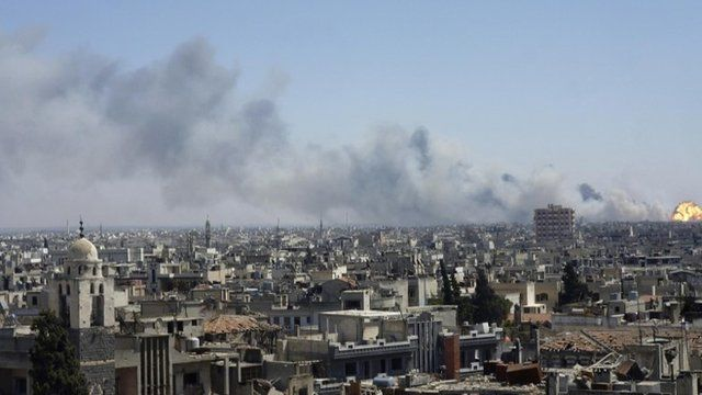 Flame and smoke rise from the district of south-eastern Wadi al-Dhahab in Homs