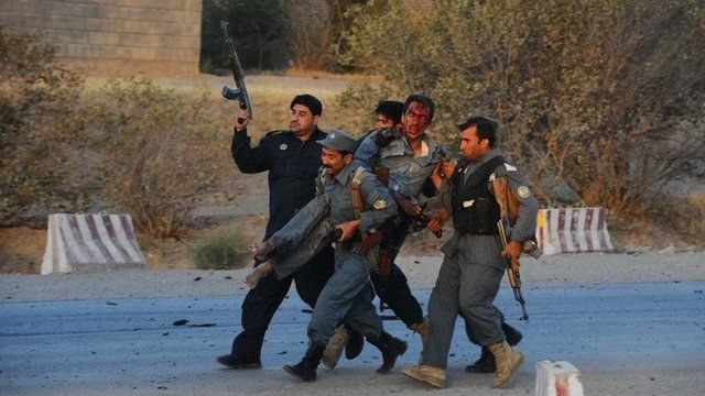 Afghanistan security forces carry a wounded police officer during an attack on the US consulate in Herat on 13 September 2013