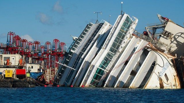 Engineers work near the wreckage of the Costa Concordia
