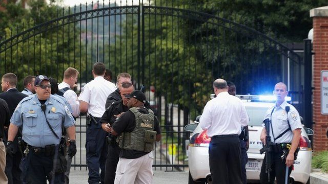 Law enforcement personnel respond to a reported shooting at an entrance to the Washington Navy Yard
